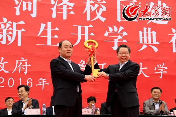 解维俊(左)向齐鲁工业大学党委副书记、校长陈嘉川交付菏泽校区